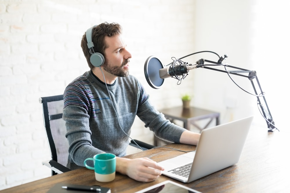 Man recording a podcast on his laptop