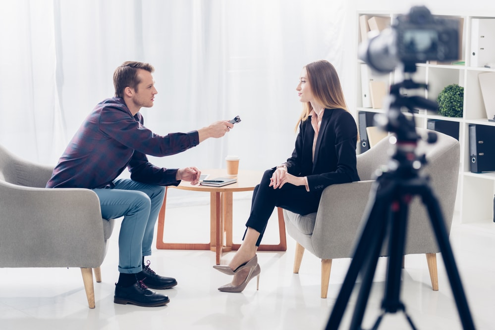 man and woman recording a podcast interview with video camera and mic